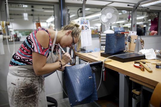 A craftswoman works on a Kelly bag at the luxury goods Hermes factory in Seloncourt