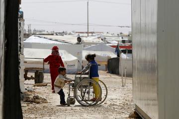 Syrian refugee children play with a wheelchair at the Al Zaatari refugee camp in Mafraq