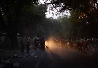 Dust engulfs cleaners as they attempt to sweep up debris left behind by anti-government protesters who continue to occupy streets outside Government House in Bangkok
