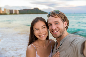 Selfie couple on Waikiki beach taking pictures with smartphone during night out walk on beach summer vacations in Honolulu, Hawaii. Travel destination. Young people having fun on hawaiian holidays.