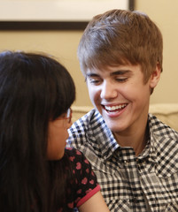 Canadian pop star Bieber smiles to a girl from northeastern Japan, the area devastated by the March 11 earthquake and tsunami, at an event at the U.S. Ambassador's residence in Tokyo