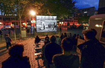 People watch a copy of a short film, one in a series of several of the first movies made in cinema history around 1895 by French brothers August and Louis Lumiere, in Lyon
