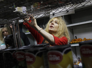Rosalinde Block, 58, reaches for canned food items at the Food Bank For New York City Community Kitchen & Food Pantry of West Harlem in New York