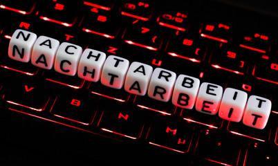 Nachtarbeit Buchstaben auf beleuchteter Tastatur