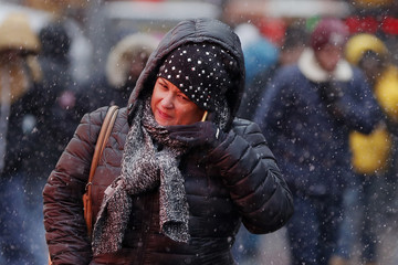 A woman covers up from the snowfall at Times Square in New York