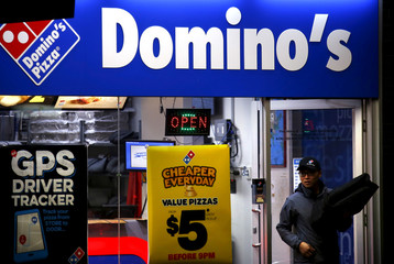 A worker carries a pizza for delivery as he exits a Domino's pizza store in Sydney, Australia