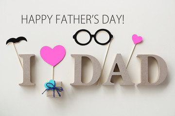 Happy Fathers Day background with wooden blocks, small gift box,  glasses and hearts.Flat lay.