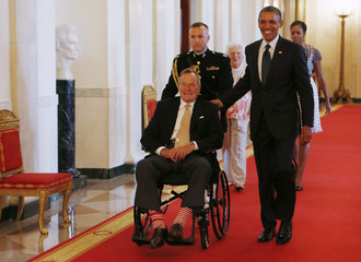 Former U.S. President Bush sits in a wheelchair as he is escorted next to U.S. President Obama in the East Room of the White House in Washington