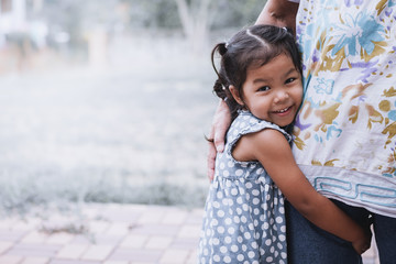 Happy asian little girl hugging her mother leg in vintage color tone