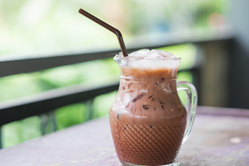 iced cocoa in glass pitcher putting on table. have blurred nature background. this image for food and beverage concept