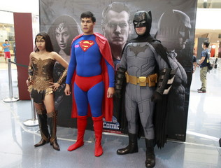 Participants wearing superhero costumes pose for pictures before the World DC Comics Super Heroes gathering in Manila