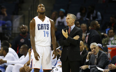 Charlotte Bobcats head coach Mike Dunlap talks with small forward Michael Kidd-Gilchrist (14) as he looks up to the scoreboardduring the second half of their NBA basketball game  against the Brooklyn Nets in Charlotte
