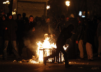 A wooden bench is set on fire by protesters during riots downtown in Bucharest