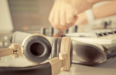 DJ music producer is turning knob on his studio equipment