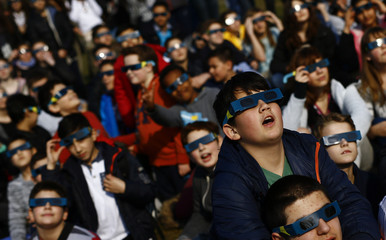 Pupils of the Deutschherren school and their teachers use protective glasses to watch a partial solar eclipse in Frankfurt