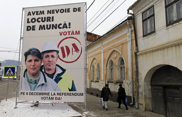 """People pass by a referendum poster reading """"We need work positions"""" in Zlatna"""