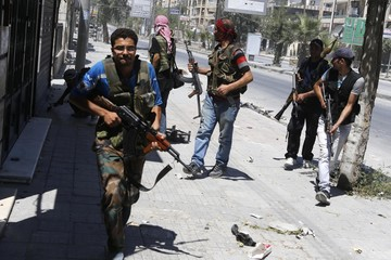 Syrian rebel fighters run for cover from heavy fighting in the Saif al-Dawla district in the centre of Aleppo city