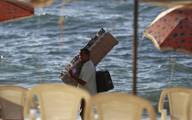 A man sells sunglasses by the sea at a public beach at Abu Qir in the Mediterranean city of Alexandria