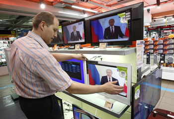 Shop assistant checks screen displaying live broadcast of Russian President Putin's annual state of nation address in Moscow