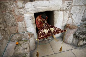 Greek Orthodox altar server leaves Church of Nativity before arrival of Greek Patriarch of Jerusalem Metropolitan Theophilos in Bethlehem
