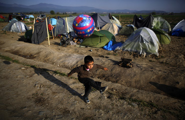 Boy plays with a ball at a makeshift camp for refugees and migrants at the Greek-Macedonian border near the village of Idomeni