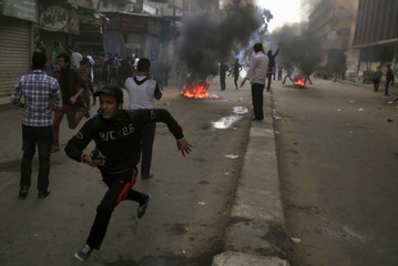 Supporters of Muslim Brotherhood and ousted Egyptian President Mursi flee and run near burning tyres, from tear gas fired by riot police and army, during clashes at El-Talbyia