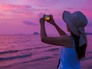 Rear view of a young woman making picture on cell telephone camera while enjoying her vacation holidays on the seashore at sunset, hipster girl photographing amazing sea landscape on her smart phone