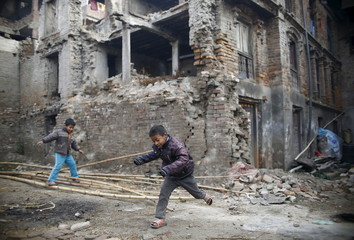 Children play near a house that was damaged during the earthquake last year, in Bhaktapur, Nepal