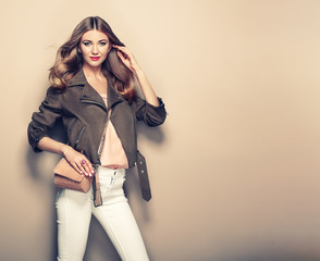 Young blond woman in brown jacket and white jeans. Girl posing on a beige background. Jewelry and hairstyle. Girl  with  brown handbag. Fashion photo