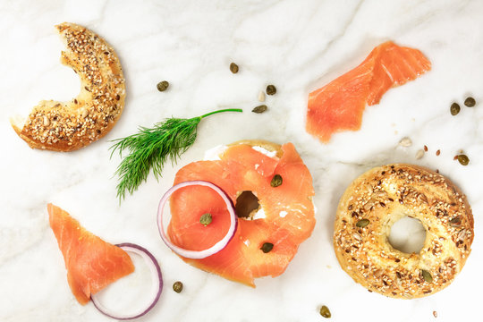 Making lox bagels, on white marble background with copyspace