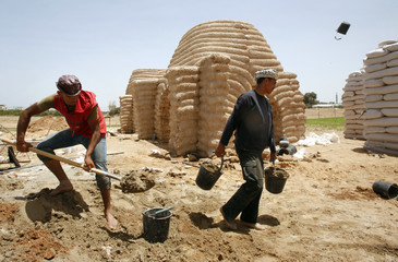 A Palestinian labourer carries buckets near structures built with sacks of sand in northern Gaza Strip