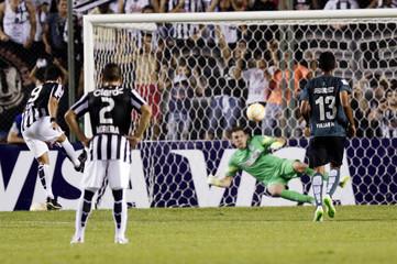 Lopez of Libertad scores a penalty against past goalkeeper Franco Armani of Atletico Nacional during their Copa Libertadores soccer match at the Nicolas Leoz stadium in Asuncion