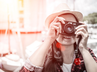 Close up Portrait of beautiful woman with retro hipster camera having fun at the beach.