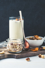 Yoghurt, muesli, nuts and dried fruits on a wooden Board over dark stone background. Vertical frame, diet, weight loss or healthy eating concept