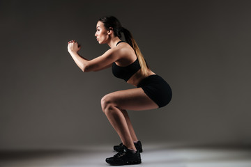 Strong sportswoman make sports exercises over grey background
