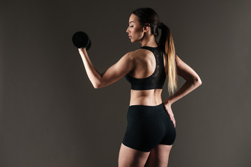 Amazing strong sportswoman make sports exercises with dumbbell