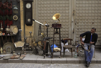 A shopkeeper smokes a hookah as he waits for customers at an old souvenir shop at a popular tourist area in the Khan el-Khalili market in old Cairo
