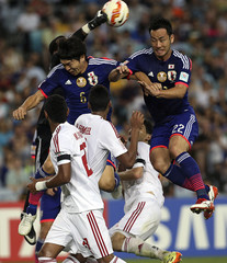 UAE's goalkeeper Majed Naser punches the ball clear from Japan's Masato Morishige and Maya Yoshida during their Asian Cup quarter-final soccer match at the Stadium Australia in Sydney