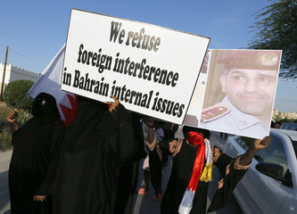 Mourners, including family members of policeman Ali, hold poster and picture of UAE police officer Shihhi, during a protest after Ali's funeral procession in Hananya
