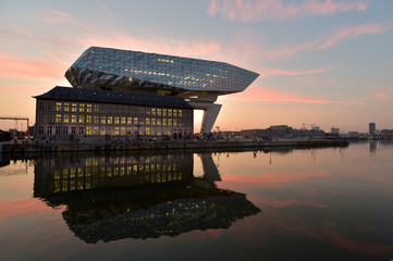 The sun rises behind the Port House, a monumental design by Zaha Hadid Architects in Antwerp