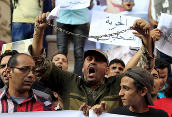 A protester holds up his hands, which are chained together, as journalists and members of the April 6 movement protest against the restriction of press freedom and demand the release of detained journalists in front of the Press Syndicate in Cairo