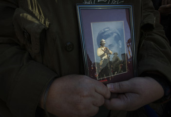 Elaine Selby holds a picture of her father Norman, who served World Word II in the Queens Own Rifles, as a  sentry standing guard is seen reflecting in the glass during Remembrance Day ceremonies at Old City Hall in Toronto
