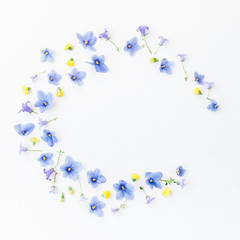 Wreath made of bellflower, pansy flowers and yellow flowers on white background. Flat lay, top view