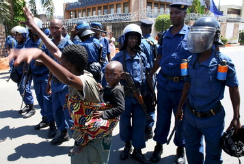 A woman dances as she carries her child in front of police during a protest by women against president Pierre Nkurunziza in Bujumbura