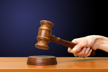 someones hand holding Wooden Law Gavel