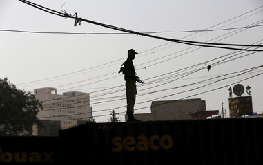 Policeman is silhouetted as he stands guard on shipping containers, put up as street barrier, ahead of the Shi'ite Muslims festival of Ashura in Karachi