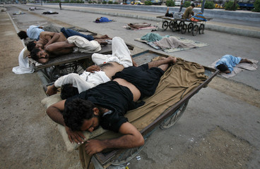 Residents sleep on carts and on a street outside their houses to escape the heat during a power outage in Karachi early morning
