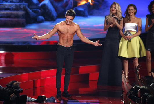 """Zac Efron poses after he threw off his shirt as he accepts the award for best shirtless performance for """"That Awkward Moment"""" as presenters Rita Ora and Jessica Alba look on at the 2014 MTV Movie Awards in Los Angeles"""