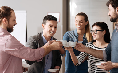 Positive colleagues touching their cups