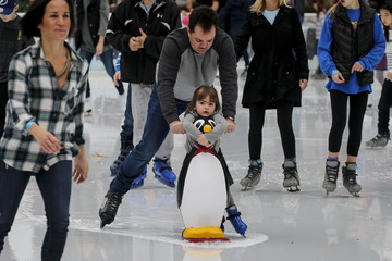 Man helps push a child, using a penguin skating aid, that makes a wake in a massive puddle at the skating rink in Bryant Park during unseasonably warm weather on Christmas Eve in the Manhattan borough of New York